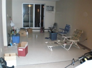photo of living room, cluttered with lawn chairs instead of furniture
