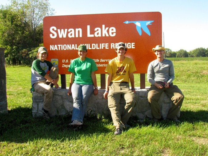 Auriel et al sitting in front of a swan lake national wildlife refuge sign