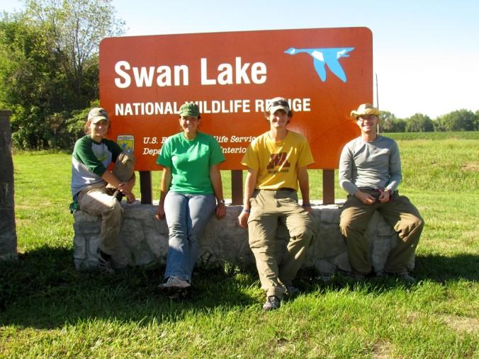 Auriel et al sitting in front of a swan lake national wildlife refuge sign