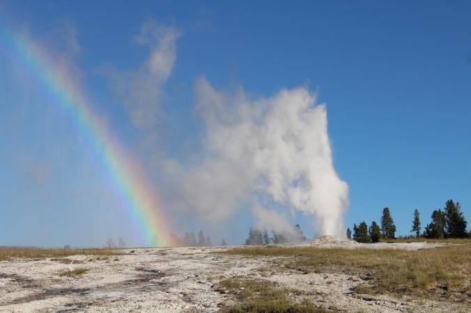 A rainbow beside a geyser.