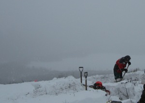 Clearing snow from a test location in the winter before the saw gets started.